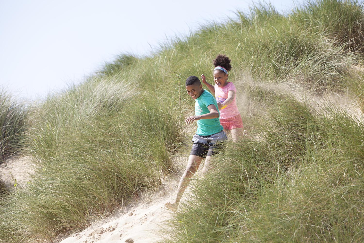 Two children playing on the sand dunes in Cornwall