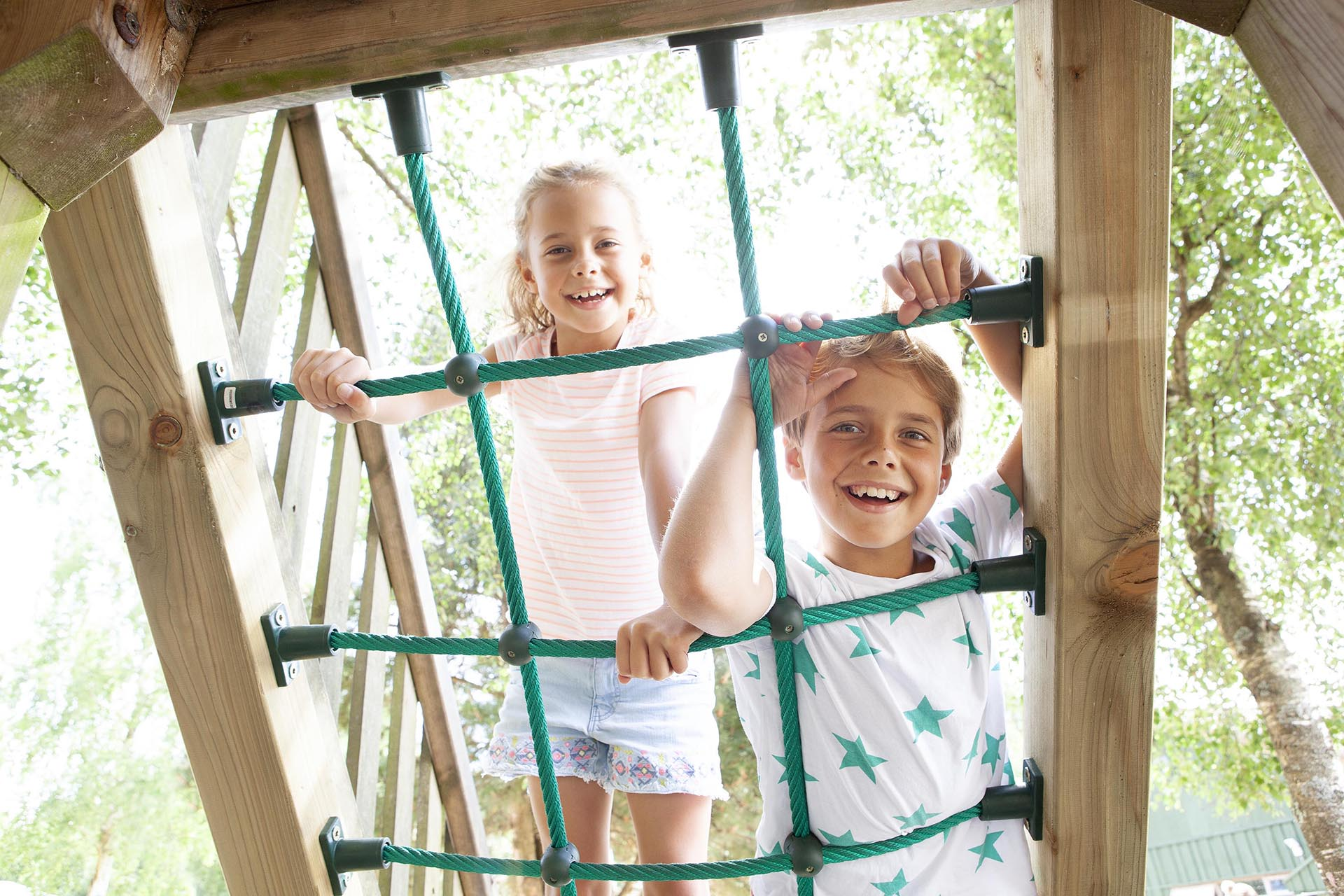 Two children climb the ropes in the playpark