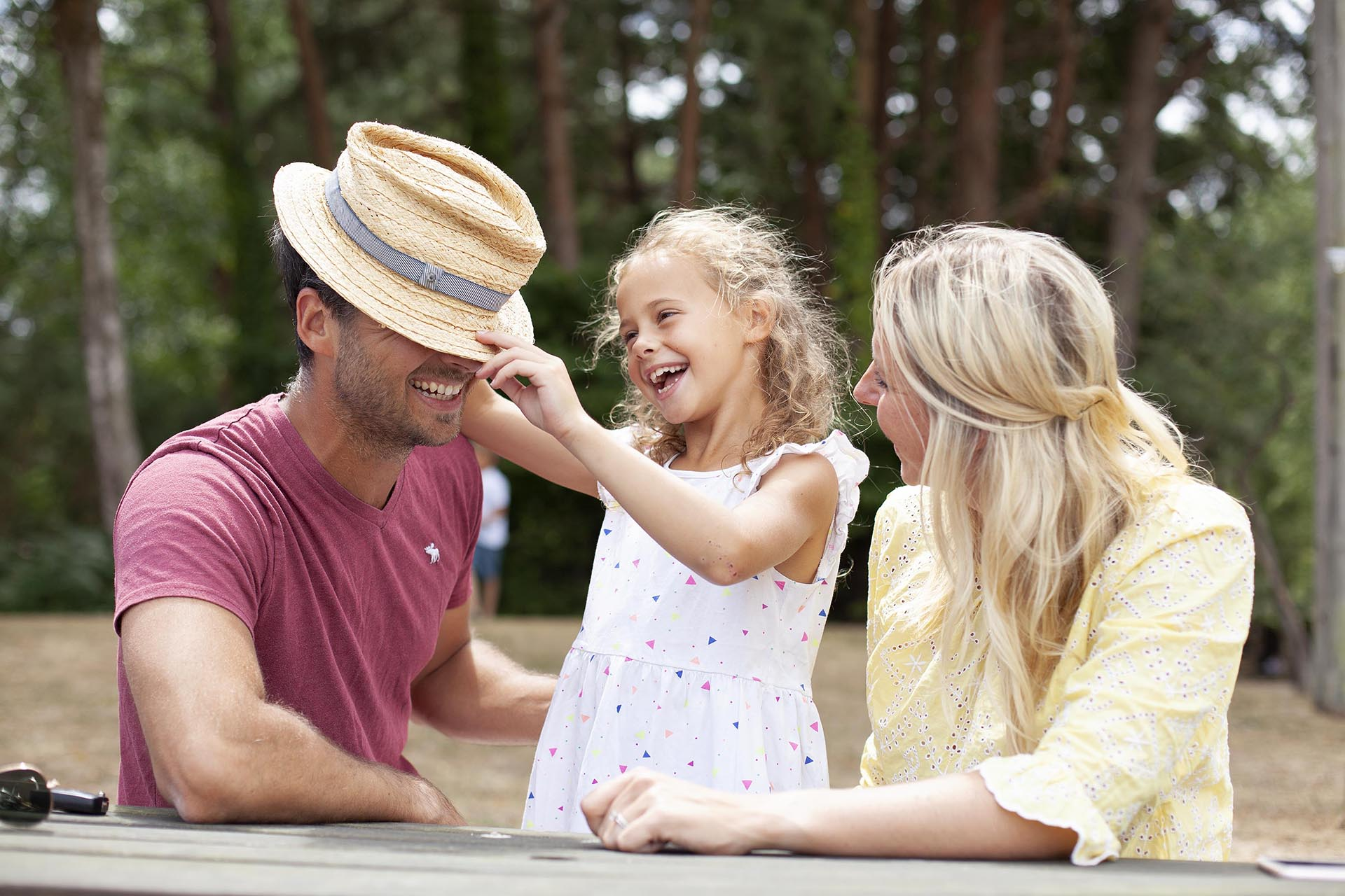 Daughter tilts dad's hat over his eyes as mum laughs