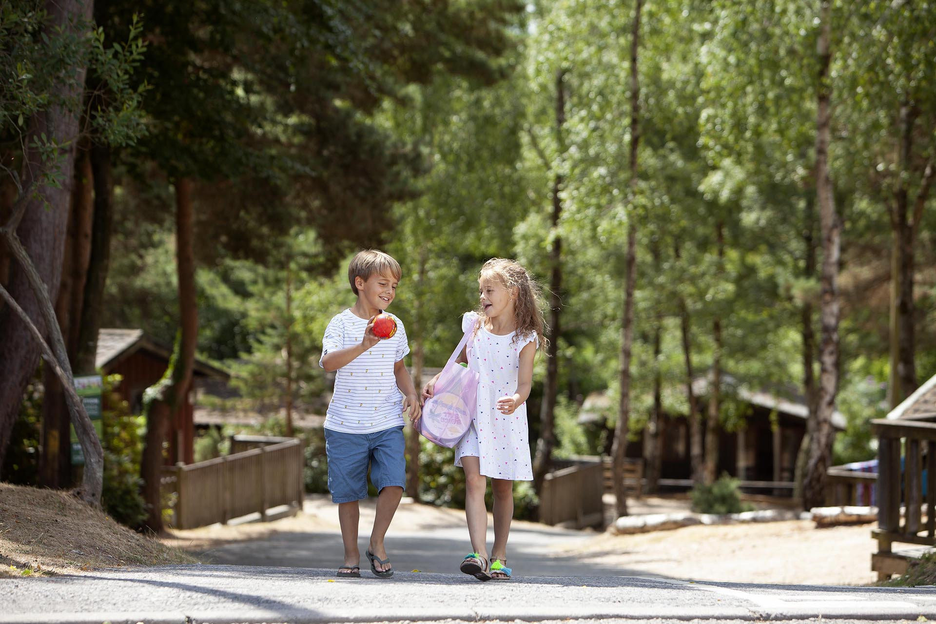 Brother and sister walk through the woodland holiday park