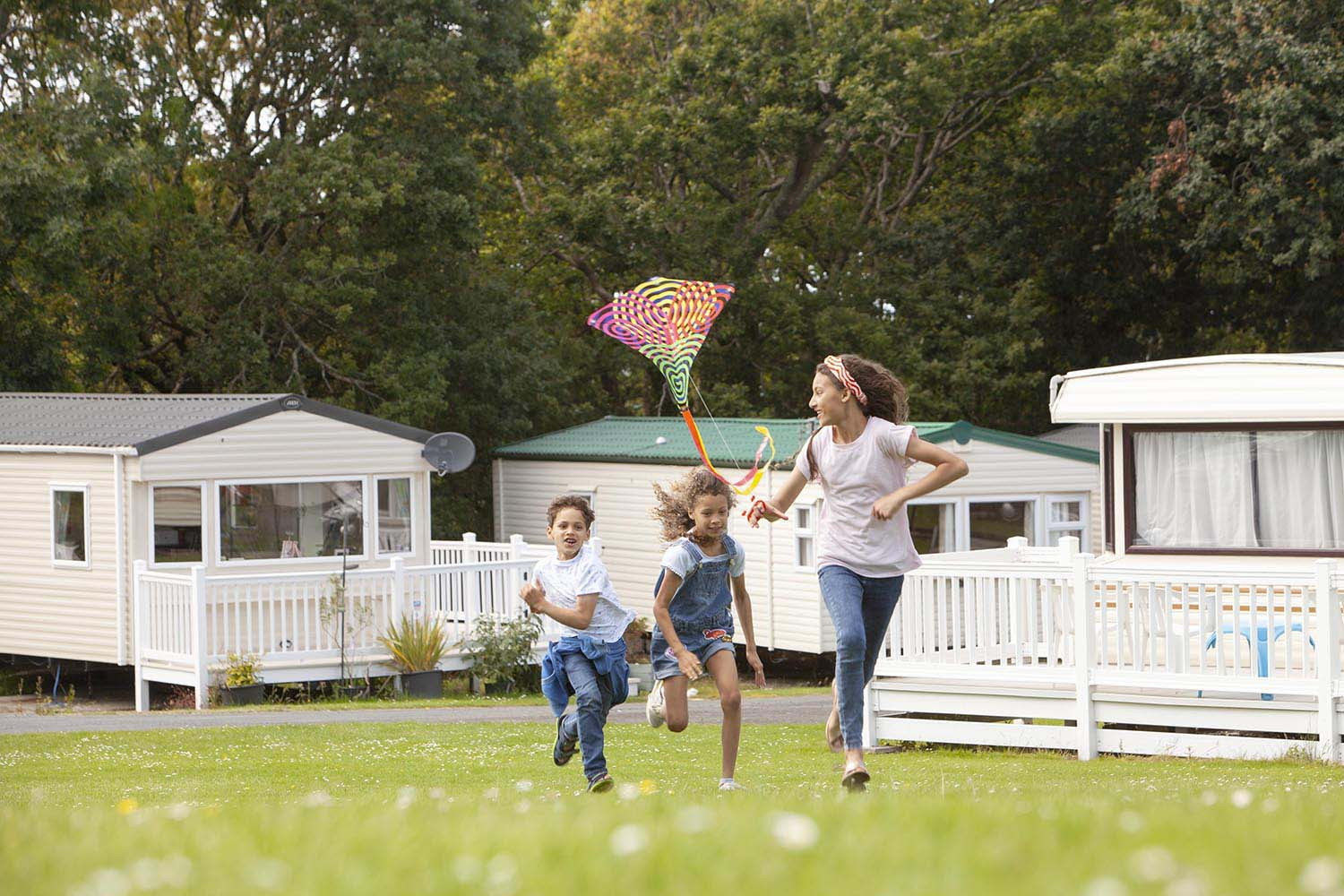 Family fly a kite in campsite holiday park Wales.