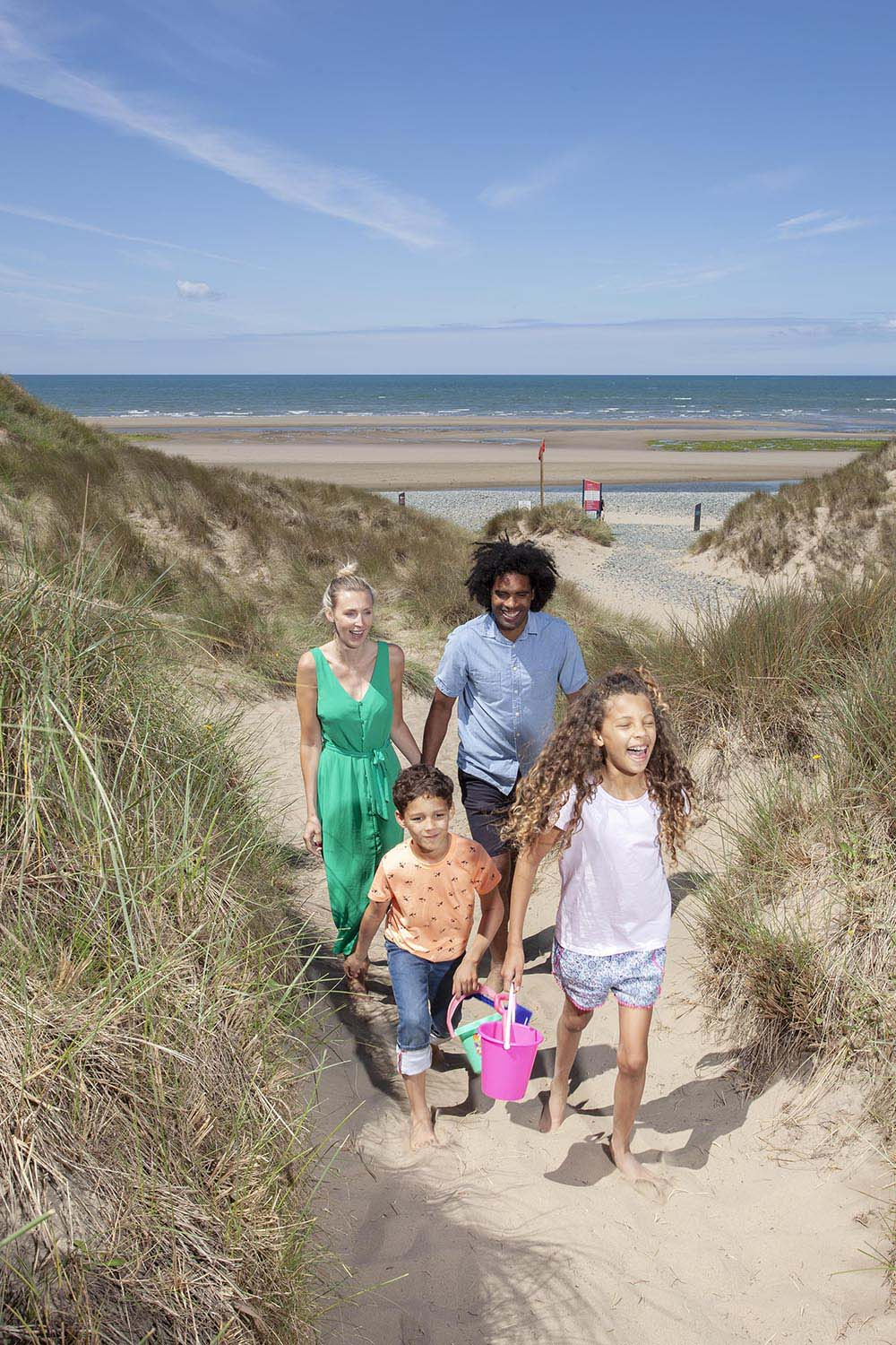 Family enjoy beach holiday in Wales campsite caravan.